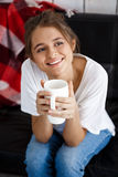 Młoda piękna dziewczyna ono uśmiecha się, trzymający filiżankę, siedzi na kanapie zdjęcia royalty free