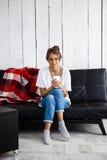 Młoda piękna dziewczyna ono uśmiecha się, trzymający filiżankę, siedzi na kanapie obraz stock