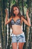 Młoda piękna dziewczyna pozuje z bamoo drzewami, Gorący lato mody pojęcie Obrazy Royalty Free
