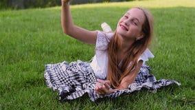 Młoda piękna dziewczyna robi selfie portretowi na trawie z telefonem komórkowym używać smartphone w zieleń parku, kłama zdjęcie wideo