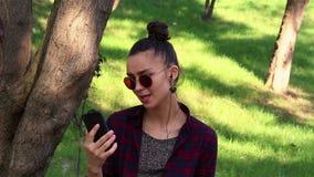 Młoda piękna dziewczyna słucha muzyka w jej smartphone, śpiewa i tanczy podczas gdy siedzący na parkowej ławce zbiory wideo
