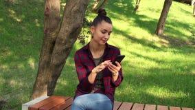 Młoda piękna dziewczyna siedzi na ławce w parku i wyszukuje ogólnospołecznej networking taśmy w jej telefonie zbiory wideo
