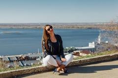 Młoda piękna dziewczyna siedzi na ceglanym parapet zdjęcia stock