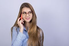 Młoda piękna dziewczyna stoi przed popielatym tłem i opowiada na telefonie z szkłami, mnóstwo czysta przestrzeń zdjęcia stock