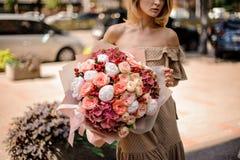 Młoda piękna dziewczyna trzyma bukiet namiętni kwiaty Fotografia Stock