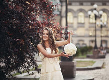 młoda piękna dziewczyna trzyma ono uśmiecha się i bukiet w białej sukni Zdjęcia Royalty Free