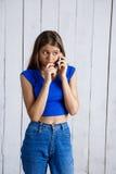 Młoda piękna dziewczyna uśmiecha się opowiadać na telefonie nad białym drewnianym tłem fotografia royalty free