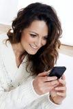 Młoda piękna dziewczyna używa mądrze telefon Zdjęcia Royalty Free