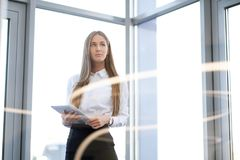 Młoda piękna dziewczyna używa pastylkę w biurze z szklanymi ścianami obrazy royalty free