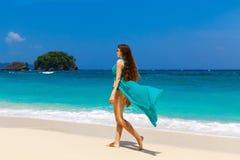Młoda piękna dziewczyna w błękit sukni na plaży tropikalny jest Obrazy Royalty Free