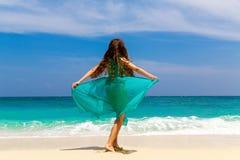 Młoda piękna dziewczyna w błękit sukni na plaży tropikalny jest Fotografia Stock