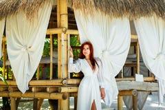 Młoda piękna dziewczyna w biel sukni stoi następnie bambusową budę dalej Fotografia Stock