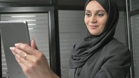 Młoda piękna dziewczyna w czarnym hijab używa pastylkę, mówi w wideo gadce, powitanie 60 fps zbiory