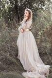 Młoda piękna dziewczyna w długiej złotej sukni z pętlą, z wiankiem kwiaty na jej głowie w wiosny zieleni ogródzie Zdjęcia Stock