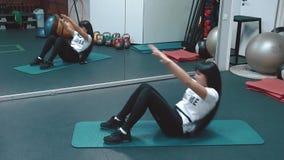 Młoda piękna dziewczyna w gym pompuje mięśnie prasa, kłama na karemate zdjęcie wideo