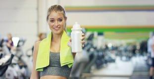 Młoda piękna dziewczyna w gym, stojaki ono uśmiecha się z ręcznikiem na jej ramieniu po trenowania i relaksującym Pojęcie: kochać zdjęcia royalty free