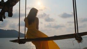 Młoda piękna dziewczyna w kolor żółty sukni na huśtawce nadmorski ocean zbiory wideo