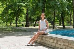 Młoda piękna dziewczyna w krótkiej biel sukni siedzi blisko fontanny Obraz Stock