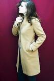 Młoda piękna dziewczyna w nabiału żakiecie na Burgundy tle Zdjęcia Stock