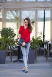 Młoda piękna dziewczyna w niebieskich dżinsach i czerwonej koszula na backgrou Obraz Royalty Free