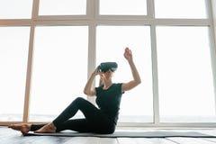 Młoda piękna dziewczyna w rzeczywistość wirtualna szkłach robi joga i aerobikom daleko Przyszłościowy technologii pojęcie nowożyt Zdjęcia Stock
