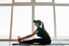 Młoda piękna dziewczyna w rzeczywistość wirtualna szkłach robi joga i aerobikom daleko Przyszłościowy technologii pojęcie nowożyt Fotografia Royalty Free