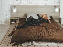 Młoda piękna dziewczyna w wieczór sukni w górę lying on the beach na łóżku po przyjęcia na tle biała ściana z cegieł zdjęcie royalty free
