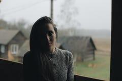Młoda piękna dziewczyna w wiosce Modeluje na tle drewniany dom w wiosce ciemności światła zdjęcie stock