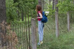 Młoda piękna dziewczyna wspina się nad ogrodzeniem z plecakiem Zdjęcia Royalty Free