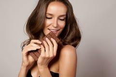 Młoda piękna dziewczyna z ciemnym kędzierzawym włosy, ogołaca ramiona i szyję trzyma czekoladowego baru cieszyć się a i smak zdjęcia royalty free