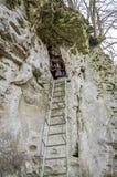 Młoda piękna dziewczyna z długie włosy w puszek kurtce, wspinającej się wysoka drabina w jamie w skale Zdjęcia Stock