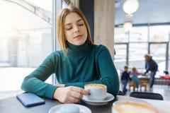 Młoda piękna dziewczyna z filiżanka kawy macaroons na talerzu, zima sezon w sklepie z kawą zdjęcie royalty free