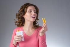 Młoda piękna dziewczyna z francuzem smaży od fasta food smilin fotografia royalty free