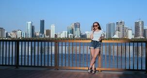 Młoda piękna dziewczyny pozycja na nabrzeżu przeciw miastu opowiada na telefonie zbiory