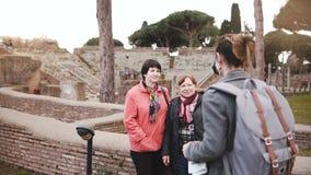 Młoda piękna Europejska dziewczyna bierze fotografię dwa starszej kobiety blisko starych historycznych ruin w Ostia, Włochy na wa zdjęcie wideo