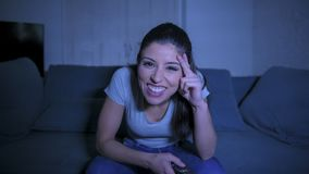 Młoda piękna i szczęśliwa łacińska kobieta trzyma TV pilota cieszy się w domu na jej 30s żyjący izbowego leżanki dopatrywania pro zdjęcia stock
