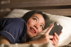 Młoda piękna i szczęśliwa Azjatycka Japońska kobieta w piżamach używać telefonów komórkowych ogólnospołecznych środki texting z j obrazy stock