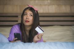 Młoda piękna i szczęśliwa Azjatycka Koreańska kobiety sypialnia w domu używać karta kredytowa interneta bankowość z telefonem kom fotografia royalty free