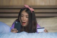 Młoda piękna i szczęśliwa Azjatycka Koreańska kobiety sypialnia w domu używać karta kredytowa interneta bankowość z telefonem kom obraz stock