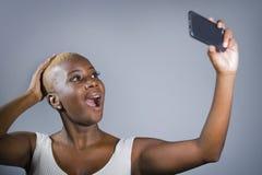 Młoda piękna i szczęśliwa czarna afro Amerykańska kobieta excited brać selfie obrazka pokazywać dumny jej ogolonego kierowniczego zdjęcie royalty free