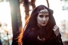 Młoda piękna i tajemnicza kobieta w drewnach, w czarnej pelerynie z kapiszonem, wizerunku lasowy elf lub czarownicie, Obrazy Royalty Free