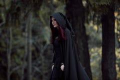Młoda piękna i tajemnicza kobieta w drewnach, w czarnej pelerynie z kapiszonem, wizerunku lasowy elf lub czarownicie, Obrazy Stock