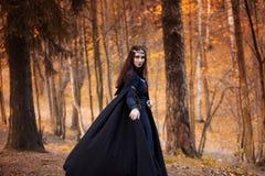 Młoda piękna i tajemnicza kobieta w drewnach, w czarnej pelerynie z kapiszonem, wizerunku lasowy elf lub czarownicie, Zdjęcia Royalty Free