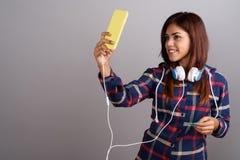 Młoda piękna Indiańska kobieta jest ubranym hełmofony i używa wiszącą ozdobę zdjęcie stock
