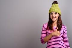 Młoda piękna Indiańska kobieta jest ubranym trykotowego kapelusz przeciw szarym półdupkom Obrazy Royalty Free