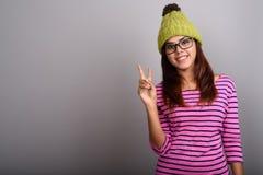 Młoda piękna Indiańska kobieta jest ubranym trykotowego kapelusz przeciw szarym półdupkom Zdjęcia Stock