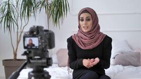 Młoda piękna indyjska dziewczyna w hijab blogger opowiada na kamerze, obliczenia, uwłaczający, gestykulujący wewnątrz, biały pokó zdjęcie wideo