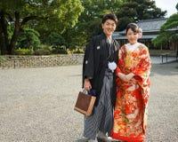 Młoda piękna Japońska para ubierająca w krajowych Japońskich kostiumach i fotografująca na ulicznym mieście Tokio, Japonia obraz royalty free