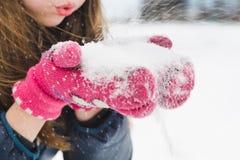 Młoda piękna jasnogłowa dziewczyna dmucha śnieg od jej ręk w parku pod miękkim puszystym śniegiem na zimnym zima dniu zdjęcie stock