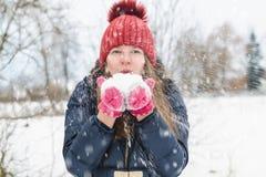 Młoda piękna jasnogłowa dziewczyna dmucha śnieg od jej ręk w parku pod miękkim puszystym śniegiem na zimnym zima dniu obraz royalty free